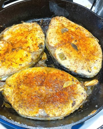 A skillet with pan fried fish.
