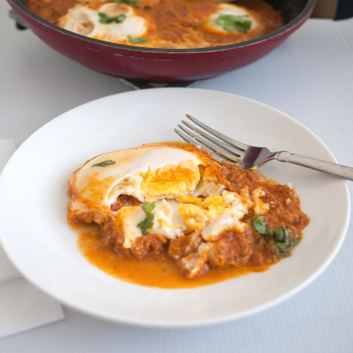 A plate with egg curry and fork.