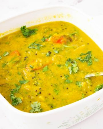 A white dish with yellow lentils dal.