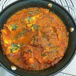 A skillet with fish curry.